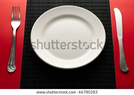 empty white plate on black table with knife and fork on red napkin by the sides of the plate