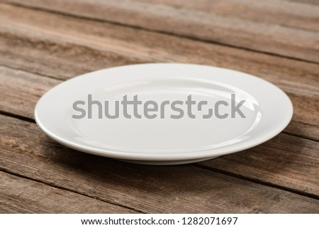 Empty white plate on wooden table. Classic dishware item for serving desserts and small portions of food.