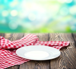 Empty white plate on wooden table decorated with picnic cloth.Food advertisement concept.