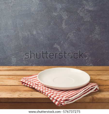 Empty white plate on wooden table over blackboard background