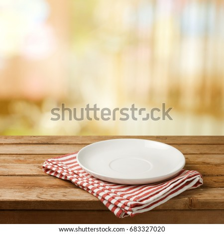 Empty white plate on wooden table over blurred bokeh background