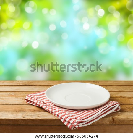 Empty white plate on wooden table over blurred bokeh nature background