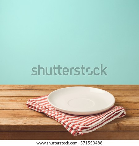 Empty white plate on wooden table over mint wallpaper background