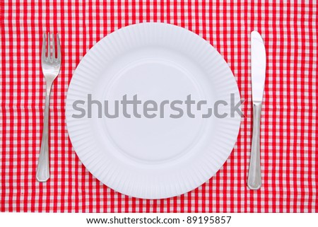 Empty white plate with fork and knife on red and white checked gingham tablecloth