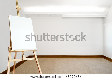 Empty white room with carpeted floor and an empty canvas on an easel