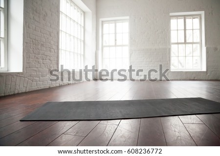 Empty white space in fitness center, white brick walls, natural wooden floor and big windows, modern loft studio, unrolled yoga mat on the floor, comfortable open area for sport and exercises
