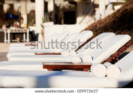 empty white sunbeds by the resort pool