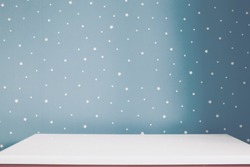 Empty white table and soft grey blue starry wall in kids room.