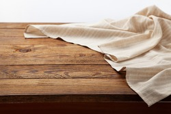 Empty white tablecloth on wooden desk perspective. Selective focus.