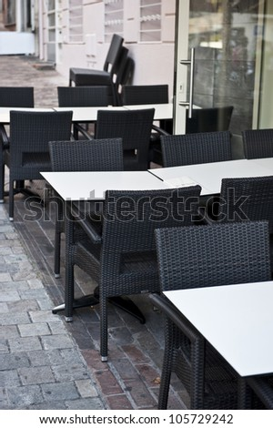 Empty white tables and black chairs outside of a restaurant cafe.
