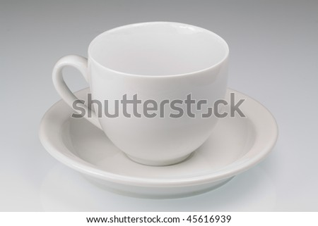 Empty white tea cup and saucer on a plain background