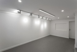 Empty white wall without frames in gallery room. Illuminated space for art exposition. Gallery lighting, spotlights No people. Showroom with a dark gray self-leveling floor.