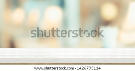 Empty white wood table and blurred soft light table in restaurant with bokeh background. product display template.Business presentation