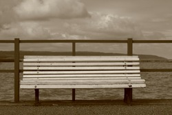 Empty white wooden made bench on pier, behind lake (sea), small fence, horizon, clouds on sky, in sepia color