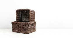 Empty wicker brown rattan basket on a white wooden background and white wall. Natural eco handmade item for home, interior. Home basket.