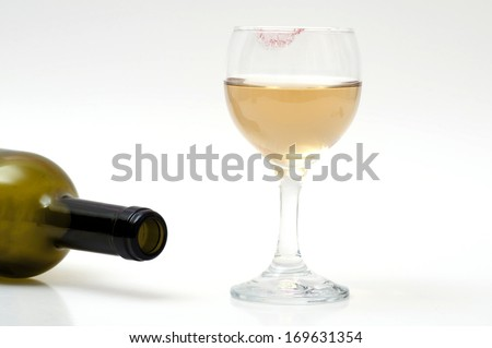 Empty wine bottle and a glass of wine with lipstick on glass.