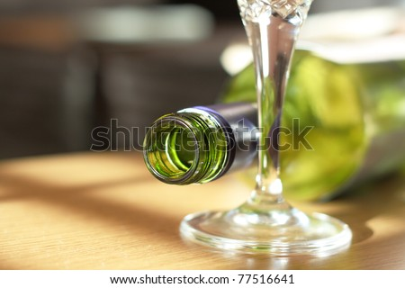 Empty wine bottle lying next to a wine glass