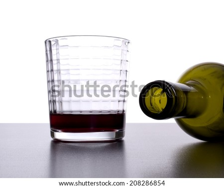 Empty wine bottle tipped over next to nearly empty glass