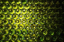 Empty wine bottles stacked-up on one another in pattern lit by the light coming from behind.