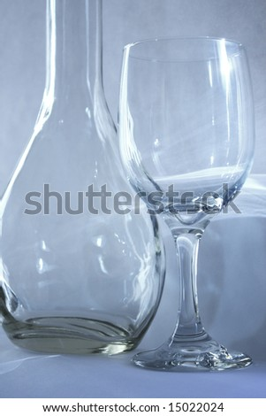 Empty wine glass and a bottle with light reflection