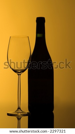 Empty wineglass and bottle of wine, still closed, with warm backlighting