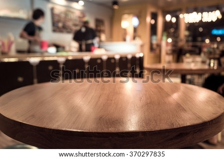 Empty wod table top with blur of people in coffee shop or cafe restaurant background.For montage product display
