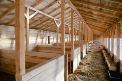 Empty woden stable/ barn with hay  on the floor