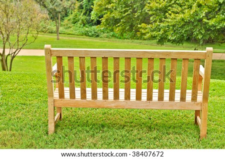 Empty wood bench on grass overlooking a path