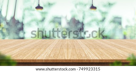 Empty wood plank table top with blur green garden coffee shop background bokeh light,Mock up for display or montage of product,Banner or header for advertise on online media,Spring and Summer concept. #749923315