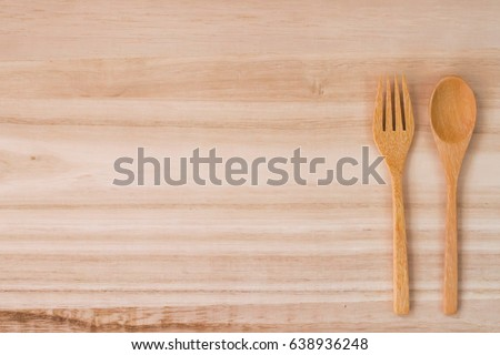 empty wood plate with wood spoon and fork on wood texture of table from top view with copyspace for text.Concept simple kitchen and food  #638936248