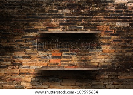 Empty wood shelf on old brick wall background, grunge industrial interior Uneven diffuse lighting version.