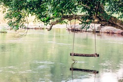 Empty wood swing hanging with rope on tree branch at river in Thailand forest with reflection on river stream. Nature for background or wallpaper with copy space.
