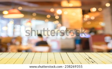 Empty wood table and blurred coffee shop  background .