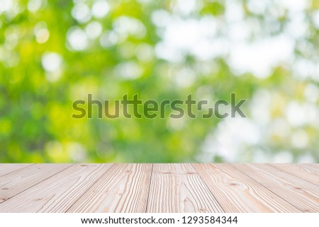 Empty wood table on green natural background in the garden outdoor. Mock up for your product display or montage #1293584344