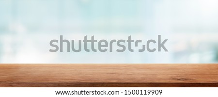 Empty wood table top and blur glass window wall building banner mock up abstract background - can used for display or montage your products.