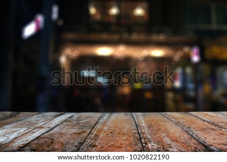 Empty wood table top and blur of brewery at night background For montage product display #1020822190