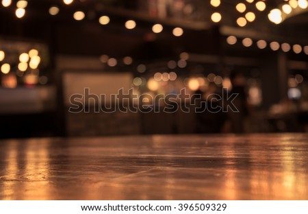 Empty wood table top and  blur of cafe restaurant in dark  night background/selective focus .For montage product display