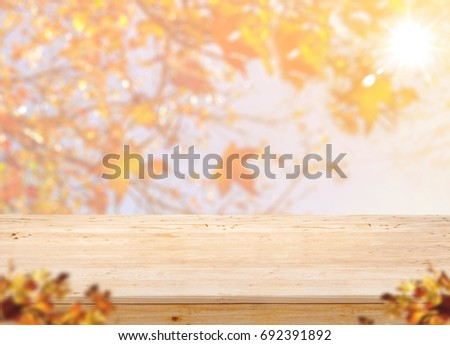 Shutterstock Empty wood table top (food stand) with blur maple leaf with sunlight and blurred maple leaf at foreground,Autumn background,Mock up for display or montage of product,banner for advertise on online