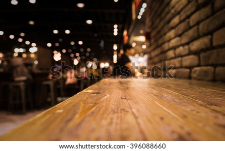 Empty wood table top of bar with blur of cafe restaurant in dark night background/selective focus .For montage product display