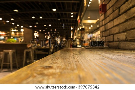 Empty wood table top of bar with blur of cafe restaurant in dark night background/selective focus .For montage product display #397075342