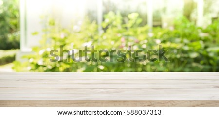 Empty wood table top on blur abstract green from garden and house in morning background. For montage product display