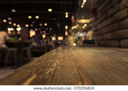 Empty wood table top on blur  cafe restaurant in dark background/selective focus .For montage product display #370296824