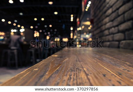 Empty wood table top on blur  cafe restaurant in dark background/selective focus .For montage product display #370297856