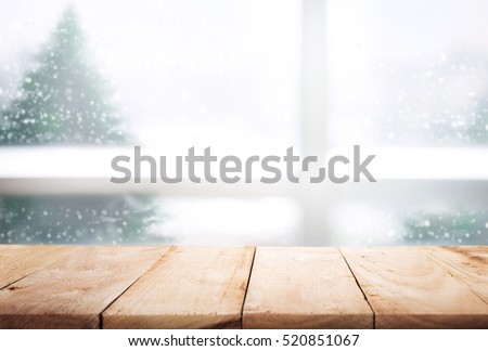 Empty wood table top on blur window view with pine tree in snow fall of winter season background,Table with window glass in the winter morning,For christmas day and new year concept.