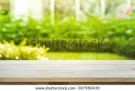 Empty wood table top on lawn green from garden in morning background. For montage product display
