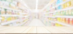 Empty wood table top with abstract supermarket grocery store aisle blurred defocused background with bokeh light for product display