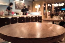 Empty wood table top with blur of people in coffee shop or cafe restaurant background.For montage product display