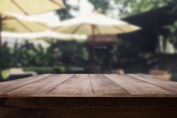 Empty wood table top with blur outdoor coffee shop with nature view for display your product or advertise montage.