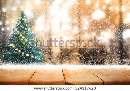 Empty wood table top with snowfall and cafe restaurant in night winter background.For holiday,christmas day and new year concept.