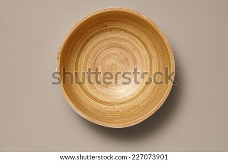 Empty Wooden Bamboo Bowl isolated on Grey Background with Real Shadow. Top View with Copy Space for Text